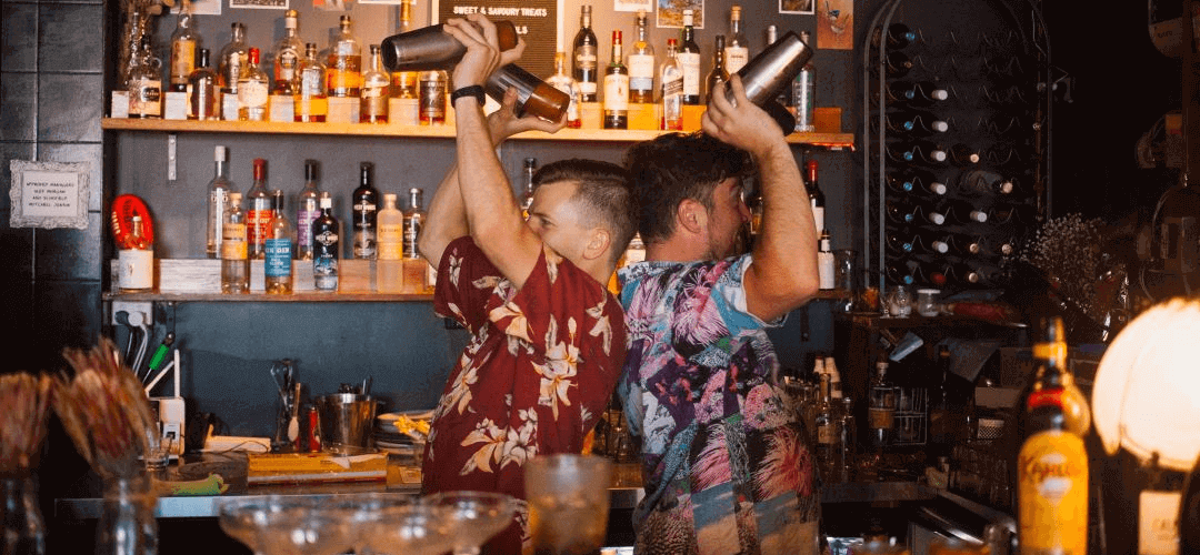 two bartenders shaking cocktails