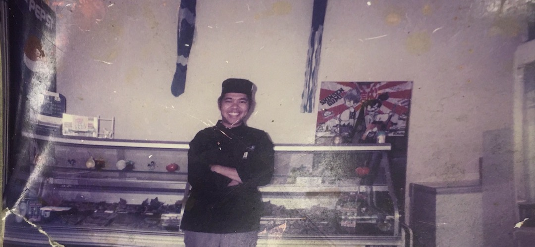Moe standing in front of the sushi fridge in his shop